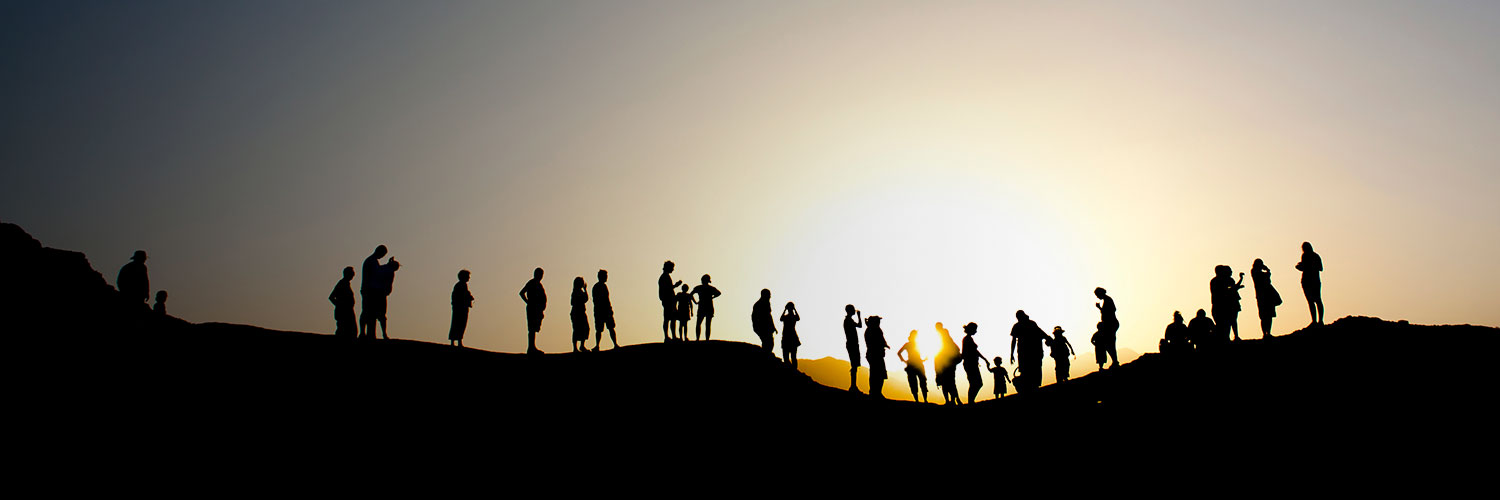 silhouette of people on mountain top